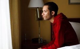Young man sitting on edge of bed due to insomnia