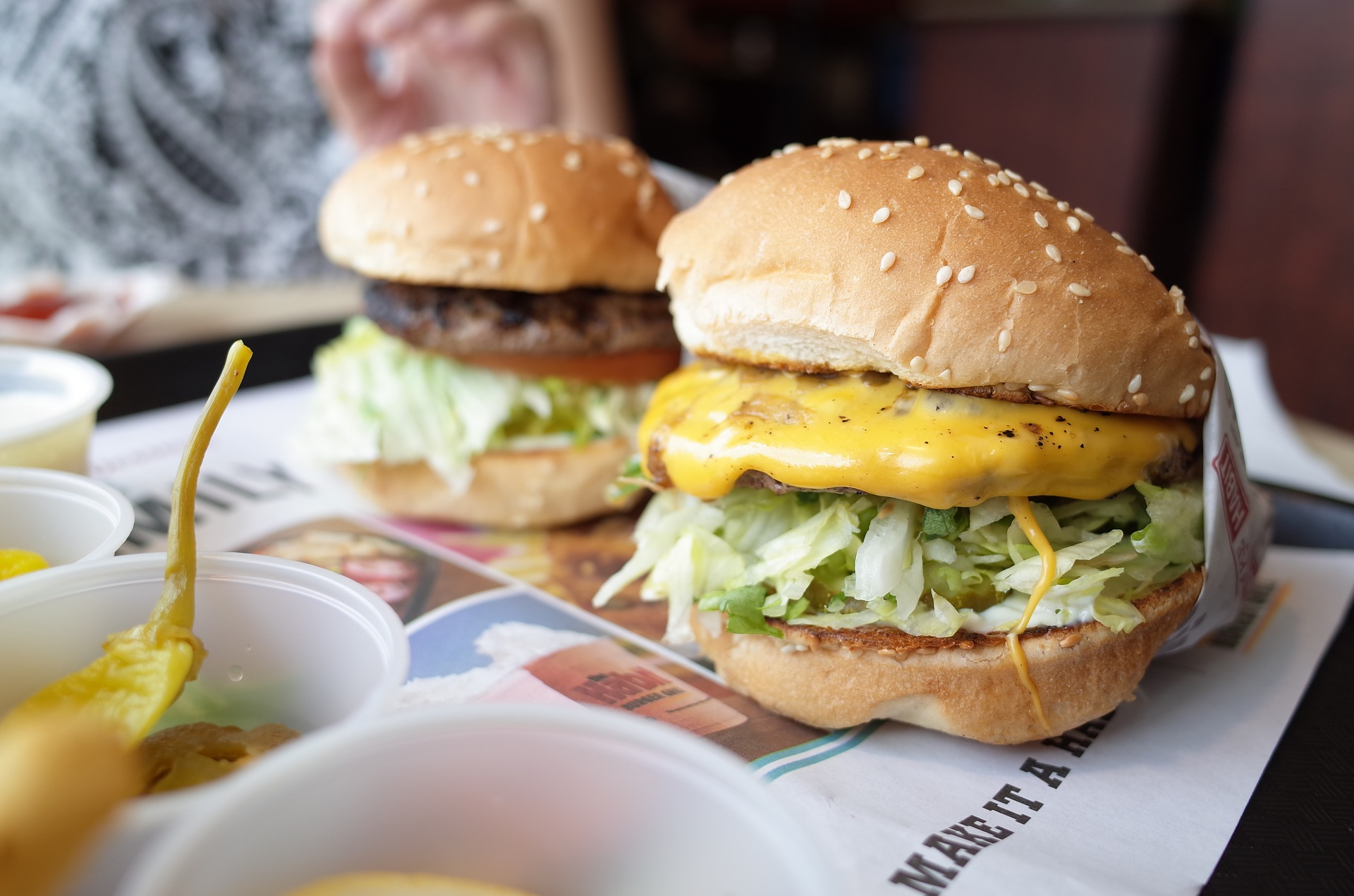 Two burgers loaded with cheese and toppings