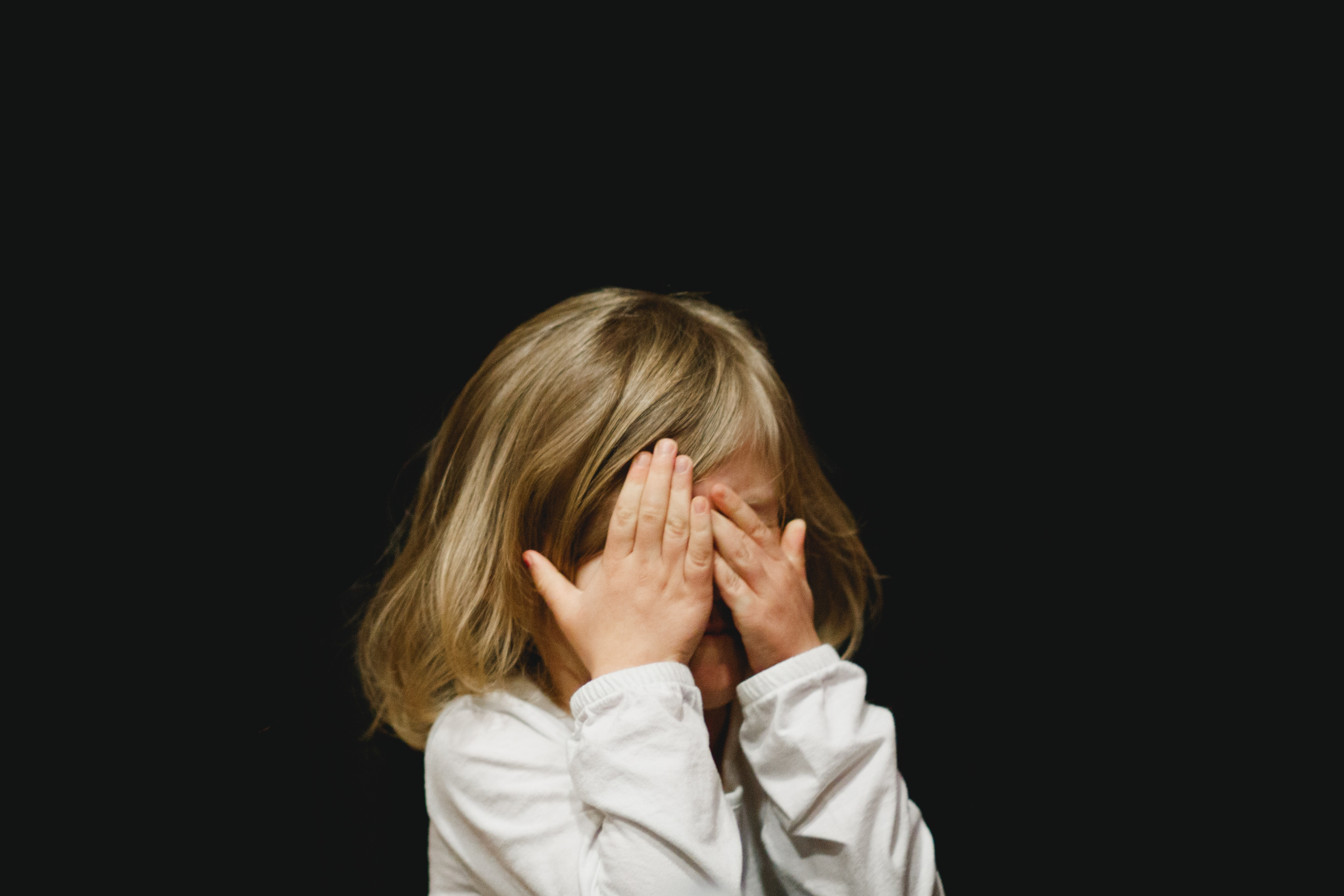 Scared little girl with hands over her eyes