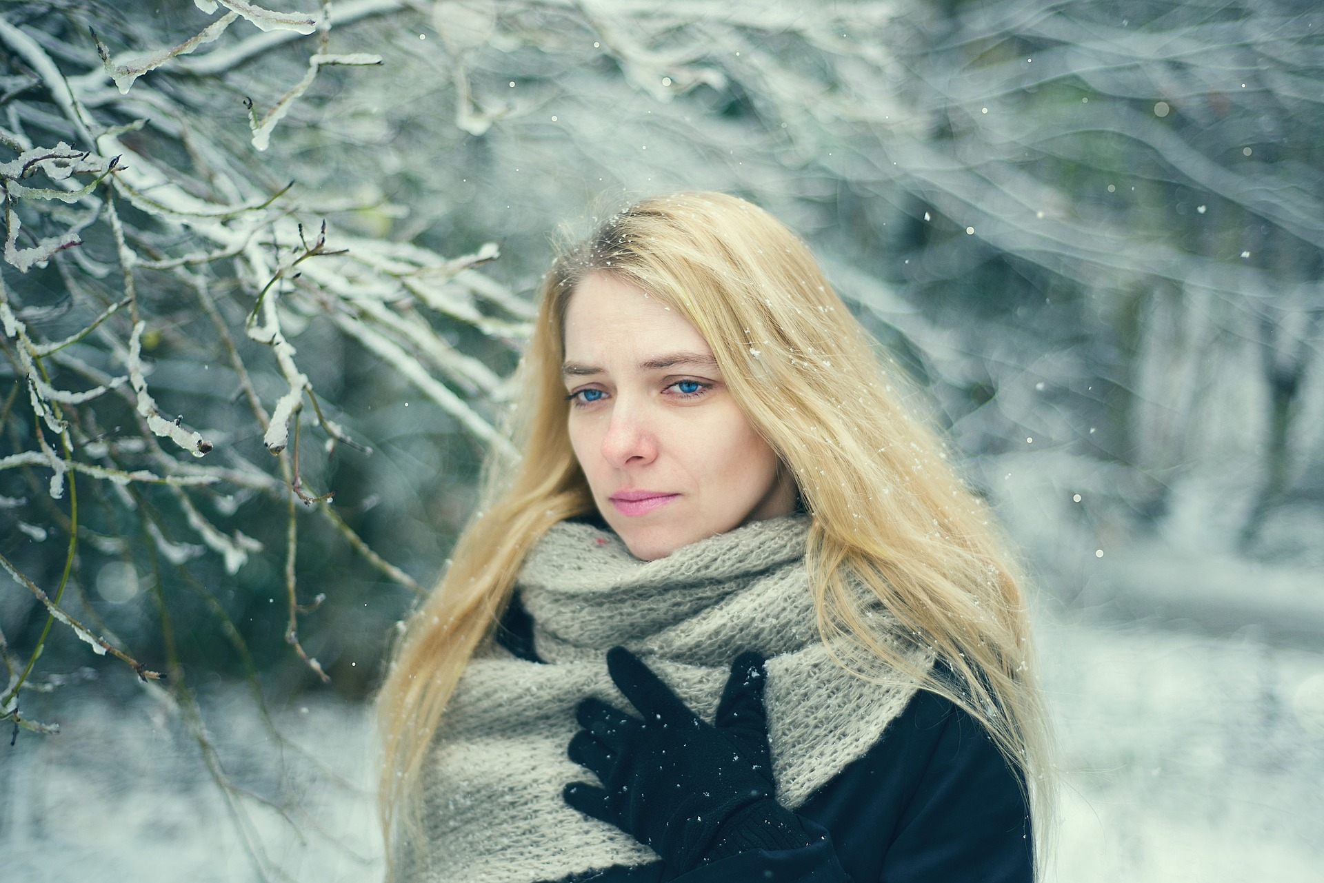 Young Lady wearing coat and scarf walking outside in the winter