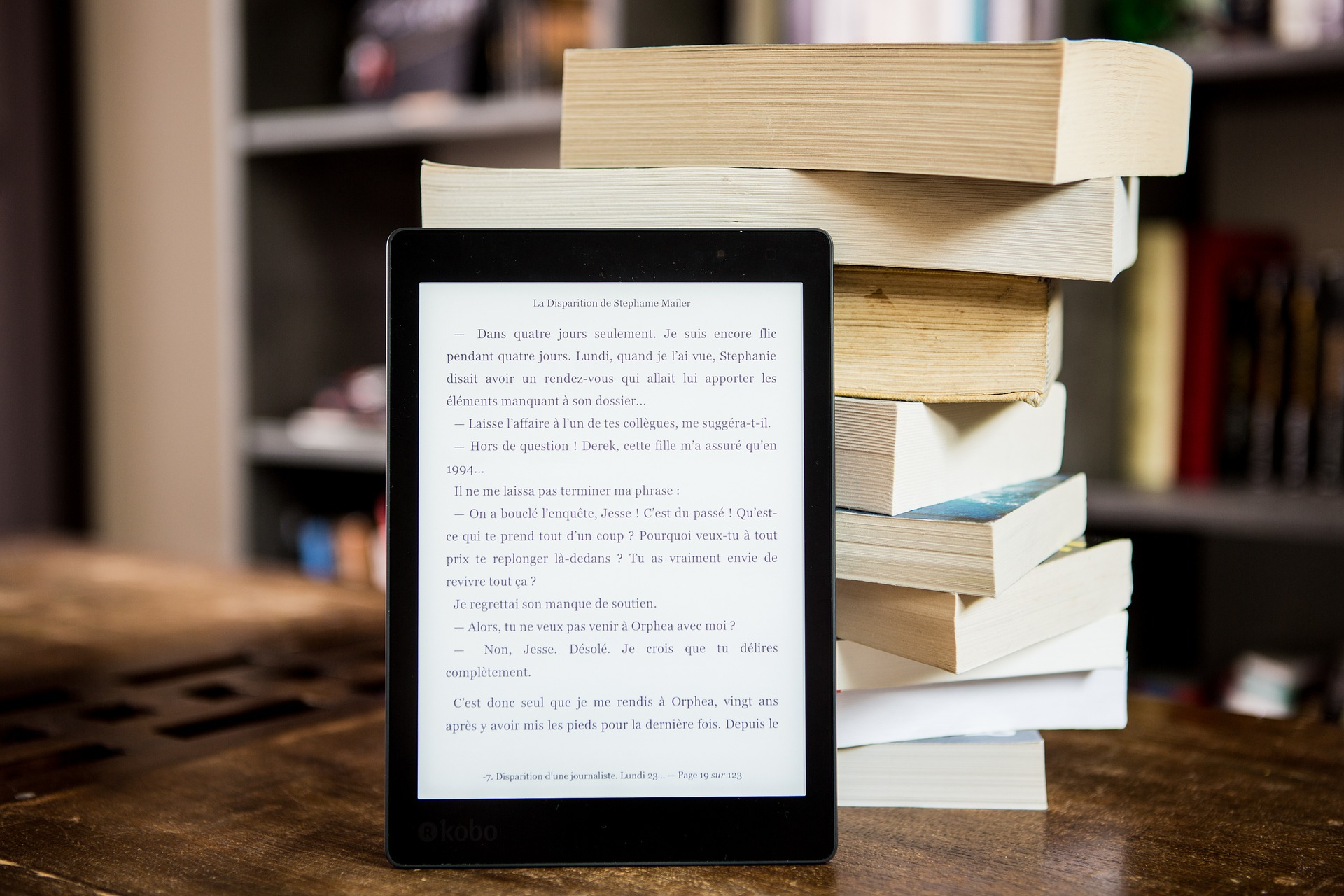 Electronic tablet in front of a stack of books