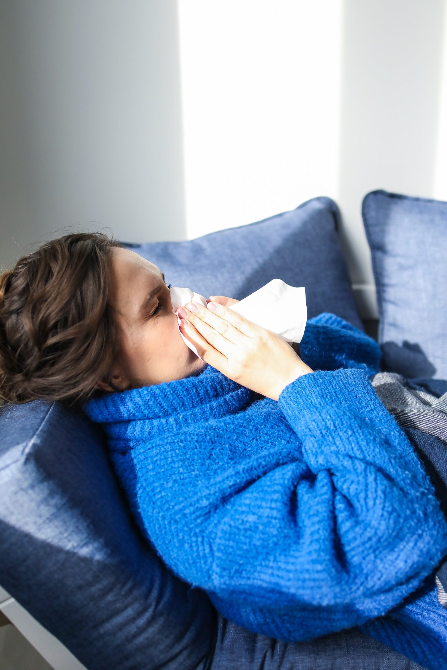 Woman in blue sweater blowing nose into a tissue