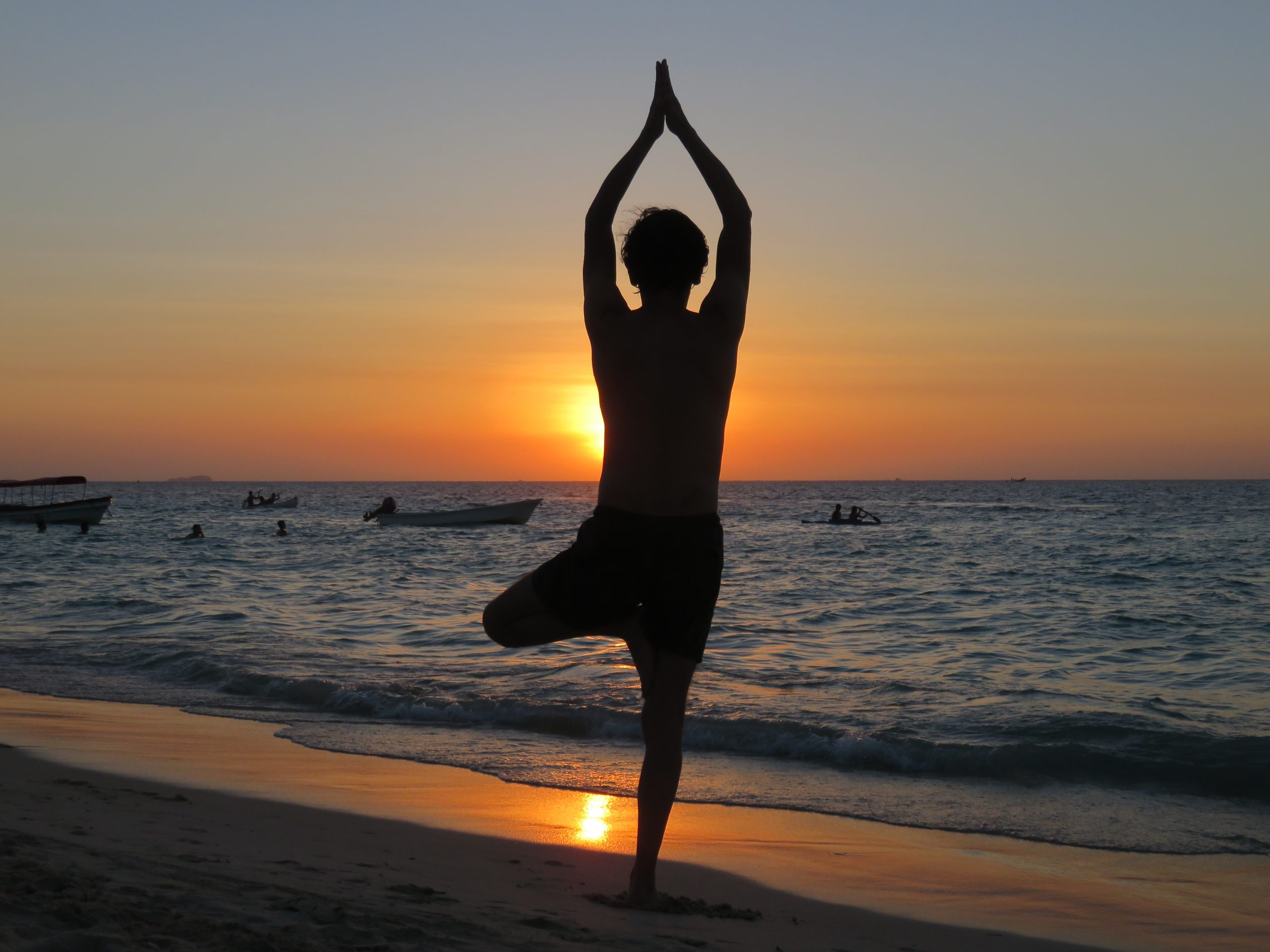 Lady in a yoga pose on the beach at sunset